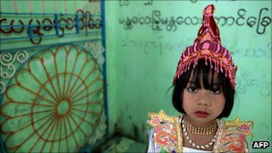 Burmese girl dressed up for ceremony marking a relative&#039;s entry into the Buddhist monkhood