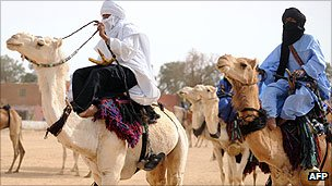 Tuareg men ride camels at the annual economic festival of Assihar