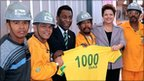 Brazilian President Dilma Rousseff and Pele with construction workers holding a Brazil shirt with 1000 days written on the back.