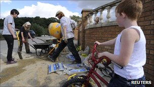 Demonstrators mix cement to construct a brick wall to block bailiffs