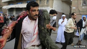 An anti-government protester carries a wounded man in Sanaa, Yemen - 18 September 2011