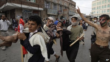 Anti-government protesters carry a wounded protestor from the site of clashes with security forces, in Sanaa, Yemen, Sept 18