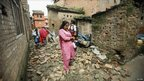 A woman, carrying her child to school, walks past quake-damaged houses in Nepal's Bhaktapur town on 19 September 2011
