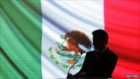 Enrique Pena Nieto, outgoing Institutional Revolutionary Party (PRI) governor in the State of Mexico, is silhouetted against the national flag before delivering his sixth and final state report in Toluca 5 September 2011