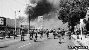 National guard troops run toward smoke in Watts, Los Angeles, 1965