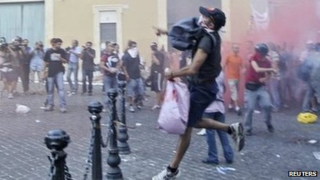Anti-austerity protesters throw flares during a protest in front of the Italian Parliament building in downtown Rome