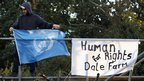 An activist attaches a UN flag to a barricade next to the main gate at Dale Farm travellers' site. (Photo by Oli Scarff/Getty Images)