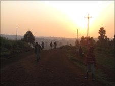 People walk along the road as dawn breaks in Kenya