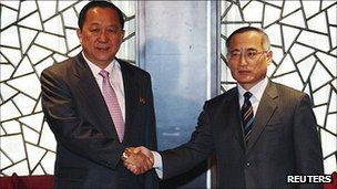 South Korea's top nuclear envoy Wi Sung-lac (R) and his North Korean counterpart Ri Yong-ho pose before their meeting in Beijing 