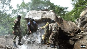 Soldiers use a jackhammer to clear boulders blocking a road in Sikkim