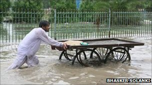 A man wades through a flooded street in Sindh