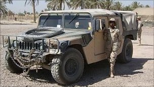 woman in military fatigues posing in front of a humvee