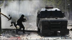 A riot police vehicle sprays tear gas at protesters in Chile