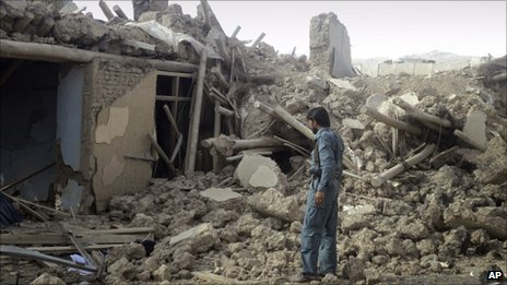 An Afghan police officer investigates the destruction from the truck bomb in Wardak on 10 September 2011