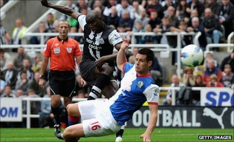 Demba Ba of Newcastle scores his team&#039;s opening goal past Scott Dann of Blackburn 