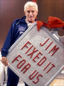 Sir Jimmy Savile with a massive Jim'll Fix It badge in 1988