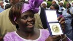 Wangari Maathai shows her Nobel prize to a cheering crowd in Nairobi in December 2004