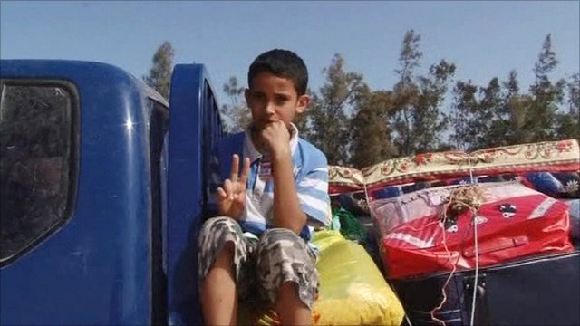 Boy on back of truck leaving Sirte