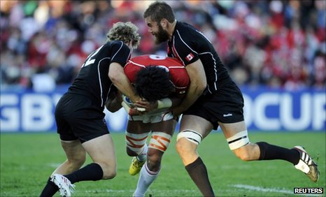 Canada's Conor Trainor (left) and Jebb Sinclair tackle Japan captain Takashi Kikutani