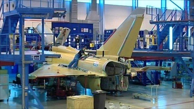 Man working on jet fighter plane
