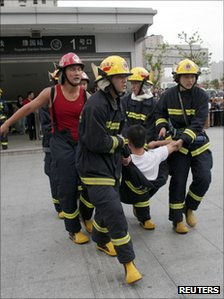 Rescue workers help an injured passenger from the subway station