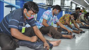 Workers at a factory in Bangladesh distressing jeans by hand