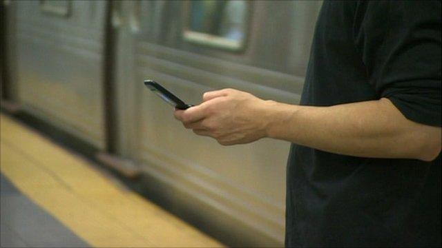 New York commuter uses mobile phone underground
