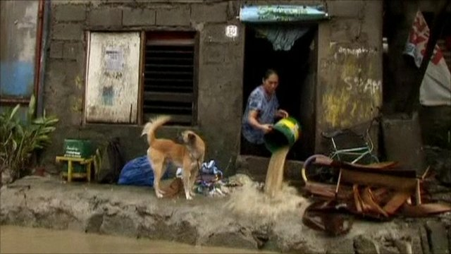 Woman in Philippines emptying water from her home