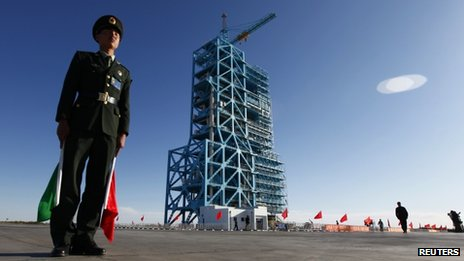 Chinese soldier stands beside Long March II-F rocket loaded with China&#039;s unmanned space module Tiangong-1 at the launch pad in the Jiuquan Satellite Launch Center, Gansu province on Wednesday