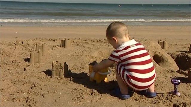 Little boy building sand castles on beach