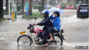 A man struggles to ride a motorbike during heavy rain brought by Typhoon Nesat in Qionghai, Hainan province on 29 Sept