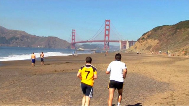 Mark McGovern jogging on beach towards the Golden Gate Bridge