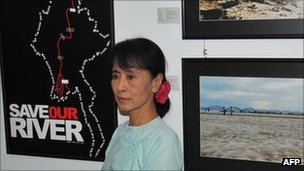 Burma democracy leader Aung San Suu Kyi poses next to campaign pictures opposing the construction of the Chinese-backed Myitsone dam, in Rangoon on 22 September 2011