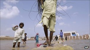 Pakistanis cross a flooded way in Badin district, in Pakistan's Sindh province, Sunday, Sept. 25, 2011.