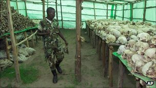 A Rwandan soldier looks at hundreds of human skulls and remains of genocide victims at the genocide memorial in Bisesero, Rwanda, in 1999
