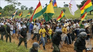 Bolivian protesters with flags flanked by riot police, 24 September