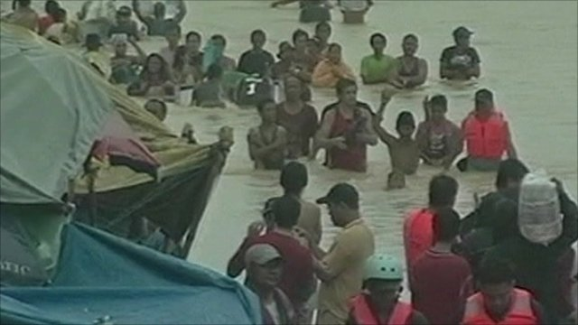 People wade through water in Philippines