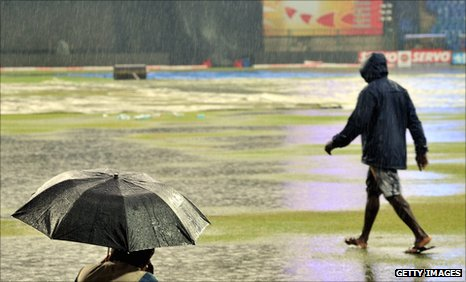 A photographer takes shelter as the rain falls in Bangalore