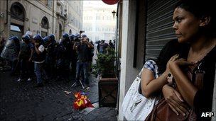 Italian people take shelter from clashes between police and protesters