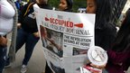 A woman reads a copy of a newspaper published by the Occupy Wall Street, 3 October 2011