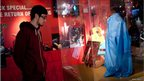 A visitor looks at items at the Elvis and Us exhibition