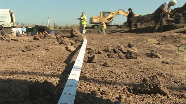 Measuring tape stretched out on the ground at the archaeological dig on the Lincolnshire fens