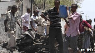 Residents gather near the covered remains of a body at the scene of an attack in Mogadishu, Somalia, on Tuesday