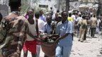 Residents carry an injured man from the scene of a suicide attack along a street in Mogadishu, Somalia, on Tuesday