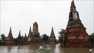 A man rows his boat past Chaiwatthanaram temple which was hit by floods in Ayutthaya province, central Thailand, 4 Oct