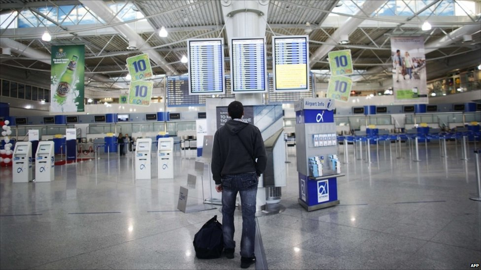 "A passenger looks for information in the departure hall of Athens"" International airport"