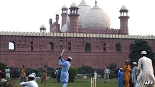 Pakistani boys play cricket near Lahore's 17th Century Badshahi Mosque