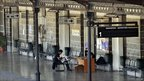 Security guards read newspapers at an empty Athens main train station