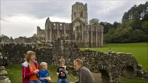 A family enjoy a picnic at Fountain's Abbey in North Yorkshire
