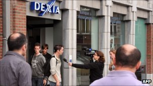 A Dexia customer is interviewed by the local media in Tournai, Belgium
